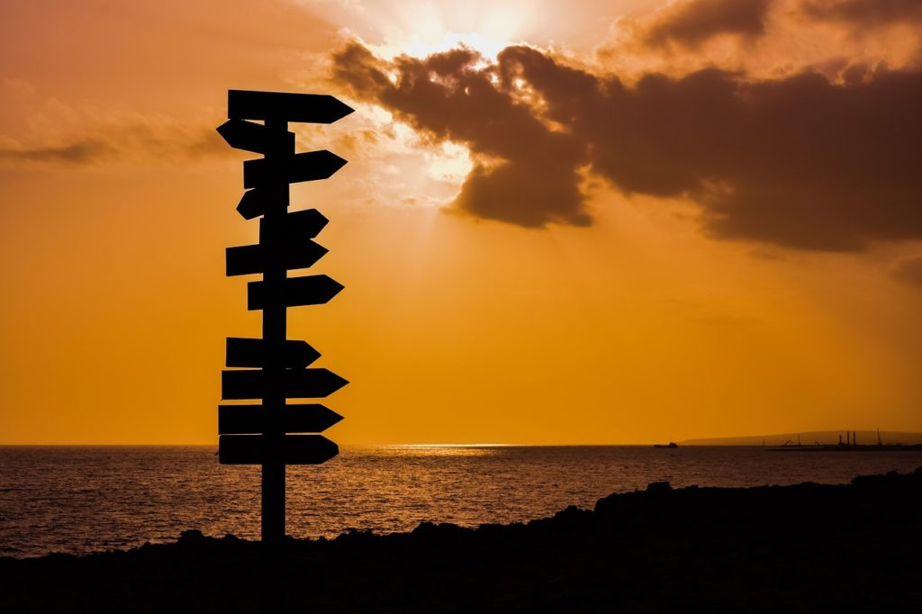 photo of sunset and directional signs